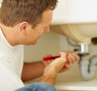 plumber fixing a bathroom sink